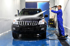 Young man washing his car with compression water. Saint Petersburg, Russia - June 26, 2014: Car maintenance, manual car washing, Worker at Car Wash Shop, Using royalty free stock photography