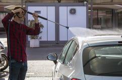 Young man washing his car at pressure car wash Royalty Free Stock Photo