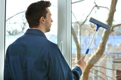 Young man washing window. In office Royalty Free Stock Images