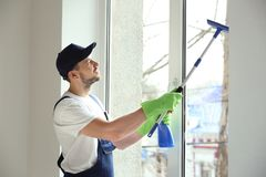 Young man washing window. In office Stock Photography