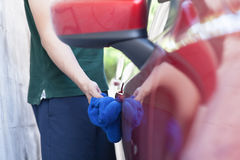 Young man washing and wiping a car in the outdoor Royalty Free Stock Photo