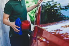 Young man washing and wiping a car in the outdoor. Young Asian man in uniform cleaning and washing a car in outdoor Stock Image