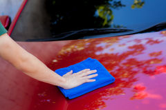 Young man washing and wiping a car in the outdoor. Close-up Stock Photography