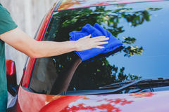 Young man washing and wiping a car in the outdoor Royalty Free Stock Photography