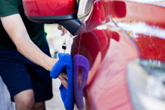 Young man washing and wiping a car in the outdoor Royalty Free Stock Image