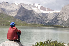 Young man watch the lake in nature. Young man with a bicycle hat watches a lake under mountain with snow,lonely Royalty Free Stock Image