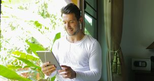 Young Man Watch Video On Tablet Computer With Earphones Sitting On Window Sill Looking To Tropical Garden. Slow Motion 60 stock video footage