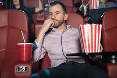 Young man watching a boring movie. Portrait of a good looking young Hispanic men looking really bored while sitting by himself at the movie theater Royalty Free Stock Photos