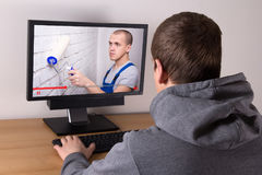 Young man watching builder`s video blog Royalty Free Stock Photos