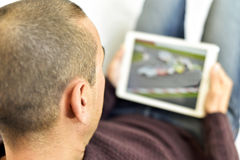 Young man watching a car race in his tablet Royalty Free Stock Photography