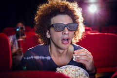 Young man watching a 3d film and eating popcorn Royalty Free Stock Photography