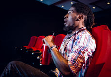 Young man watching a film and drinking soda Stock Photography