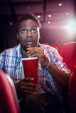 Young man watching a film and drinking soda Stock Images
