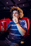 Young man watching a film and drinking soda Royalty Free Stock Photo