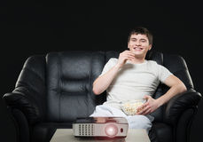 Young man watching a football broadcast Stock Photos