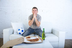 Young man watching football game on television nervous and excited suffering stress praying god for goal. On sofa couch at home with ball , beer bottle and Royalty Free Stock Image
