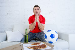 Young man watching football game on television nervous and excited suffering stress praying god for goal. On sofa couch at home with ball , beer bottle and Stock Image