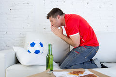 Young man watching football game on television nervous and excited suffering stress praying god for goal. On sofa couch at home with ball , beer bottle and Stock Photography
