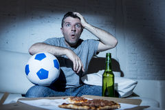 Young man watching football game on tv nervous and excited suffering stress on couch Royalty Free Stock Photo
