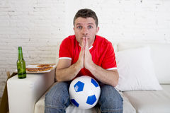Young man watching football game on tv nervous and excited suffering stress praying god for goal Stock Photos