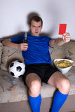 Young man watching football on tv at home. Young attractive man watching football on tv at home and showing penalty card Royalty Free Stock Photography