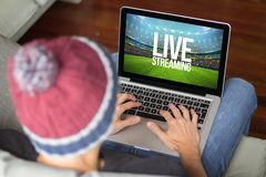 Young man on the sofa live streaming. Young man watching live streaming sports event. All screen graphics are made up stock photo