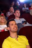 Young man watching movie in cinema. Young men sitting in multiplex movie theater, watching movie, smiling Stock Photography