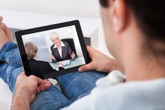 Young man watching movie on tablet pc Stock Images