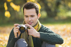 Young man watching photographs on digital camera in park during autumn Royalty Free Stock Photo
