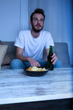 Young man watching a sad movie at night with chips and beer Royalty Free Stock Photo