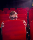 Young man watching a scary 3d film Stock Images