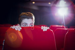 Young man watching a scary film Royalty Free Stock Image