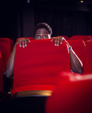 Young man watching a scary film Stock Photo