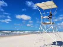 Young man watching the sea shore from a rescue tower against the blue sky stock photography