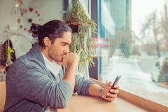 Young man watching smartphone and biting fist in worried expression. Closeup portrait of a handsome guy wearing white shirt, gray blouse sitting near window at royalty free stock photo
