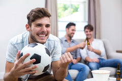 Young man watching soccer match while friends in background Stock Photo