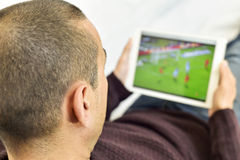 Young man watching a soccer match in his tablet. A young man lying on the couch watches a soccer match in streaming in his tablet computer Stock Photos