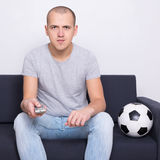 Young man watching soccer on tv at home Stock Photos