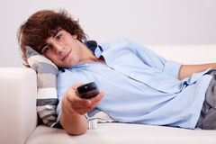Young man, watching television with the command Stock Photography