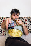 Young man watching television, eating potato chips and drinking Stock Image