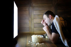 Young man watching television at home on the floor. And eating popcorn Stock Photos