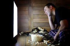 Young man watching television at home on the floor. And eating popcorn Stock Photo
