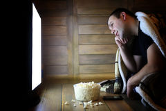 Young man watching television at home on the floor. And eating popcorn Royalty Free Stock Photos