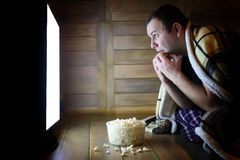 Young man watching television at home on the floor. And eating popcorn Royalty Free Stock Photo