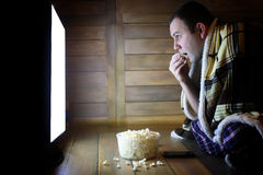 Young man watching television at home on the floor. And eating popcorn Stock Image