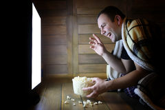 Young man watching television at home on the floor. And eating popcorn Stock Photography