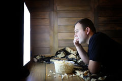 Young man watching television at home on the floor. And eating popcorn Royalty Free Stock Photography
