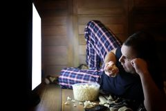 Young man watching television at home on the floor. And eating popcorn Stock Images
