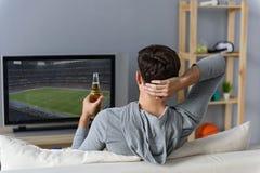 Young man watching television at home Royalty Free Stock Image