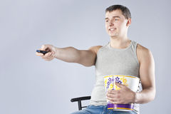 Young man watching television with popcorn Royalty Free Stock Photo